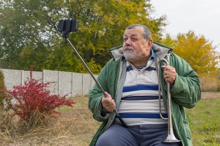 ridiculous: Ridiculous senior man making faces while doing selfie outdoor Stock Photo