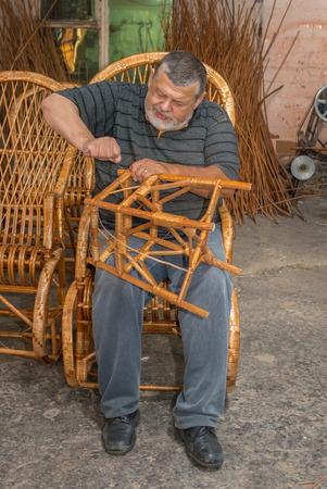stool: Ukrainian master of wicker-work making a stool