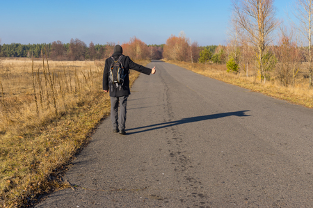 roadside stand: Mature hitchhiker walking on a road in Ukrainian rural area at fall season