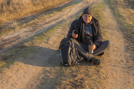 road autumnal: Very tired hiker is ready to drink some tee sitting on rural road at autumnal evening Stock Photo