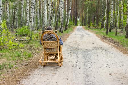 debility: Elderly man is having rest in forest sitting on a wicker rocking-chair Stock Photo