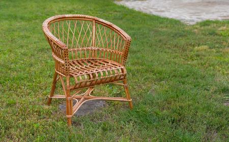 debility: Empty wicker chair in the garden