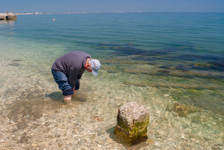 foots: Man wet foots in cold Black Sea at spring season