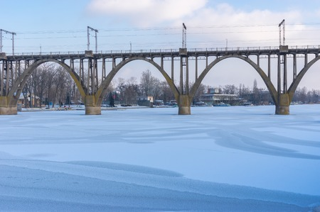 dnepr: Arched bridge on winter river Dnepr in Dnepropetrovsk city, Ukraine Stock Photo
