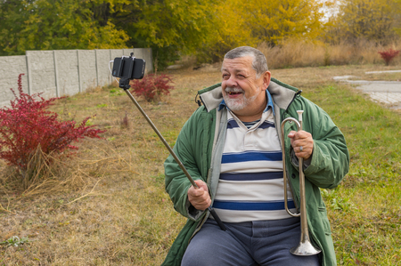 horn like: Outdoor portrait of  senior man smiling while doing selfie outdoor for online social networking service Stock Photo