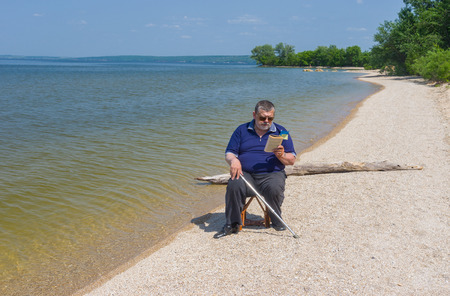 dnepr: Senior man reading book sitting on a beach of Dnepr river in Ukraine