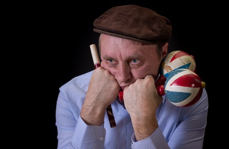 woodwind: Portrait of sad mature musician with Ukrainian woodwind instrument sopilka and maracas