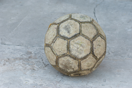 unequal: Old football (soccer ball) on a concrete surface