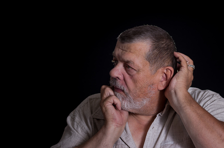 desperately: Portrait of senior man desperately thinking about life problems in the darkness