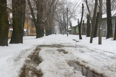 driving conditions: Dnepropetrovsk, Ukraine - January 18, 2016: Street with big puddle in suburb of the Dnepropetrovsk city at snowy winter day