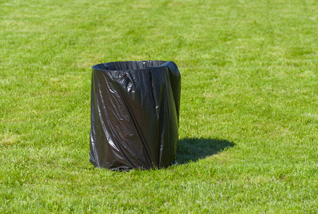 polyethylene: Garbage can in polyethylene package on a green lawn Stock Photo