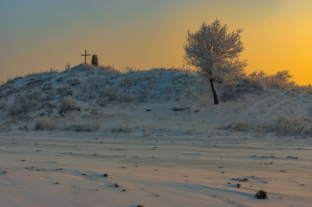 tumulus: Winter Landscape with ancient burial mound with cross and lonely apricot tree at sunset time Stock Photo