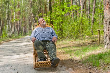 slack: Senior man is having rest in forest sitting on a wicker rocking-chair