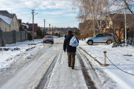 winter thaw: Novooleksandrivka village, Dnepropetrovsk oblast, Ukraine - January 29, 2016: Man carrying purchases from a remote local shop walking on a snowy, slippery street covered with melting snow and ice at winter day