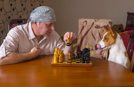 ludicrous: Young dog and mature man playing chess in a family tournament