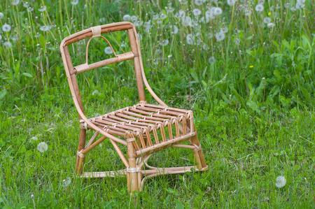 debility: Handmade wicker chair for kids in spring grass