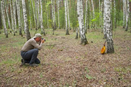 mandolin: Mature photographer making an outdoor photo of mandolin