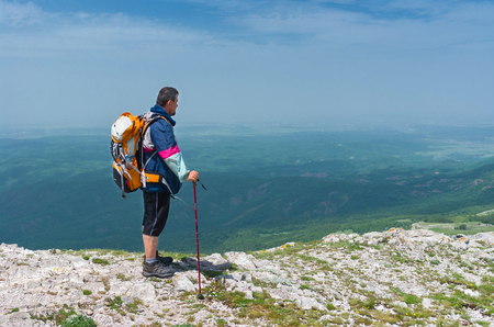admires: Crimean mountains, Ukraine - May 24, 2013: Hiker admires the scenery of the spring mountains Editorial