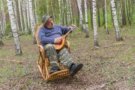 holiday maker: Senior man is having rest in birch forest, sitting on a wicker rocking-chair and holding mandolin