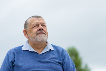 Outdoor portrait of a bearded senior man looking up with hope
