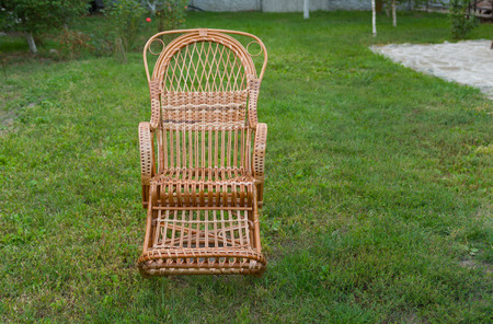 holiday maker: Empty wicker rocking-chair in the garden