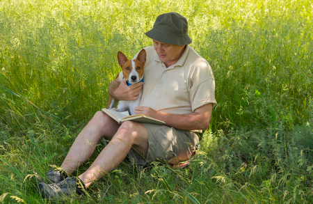 laughable: Mature man reading to young dog interesting book under a tree shadow at spring season Stock Photo