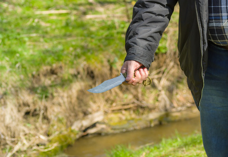 selfmade: Man holding self-made knife over spring background Stock Photo