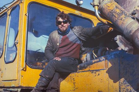 prospector: Península de Chukchi, URSS - 15 de abril 1983: conductor del tractor soviético joven que tiene poco descanso en el trabajo de extracción de oro más allá del círculo polar.