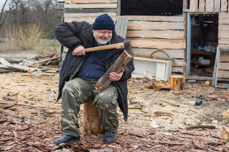 log out: Old farmer is trying to pull out an axe from log Stock Photo