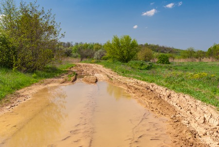 loamy: Spring landscape with big puddle on an earth road