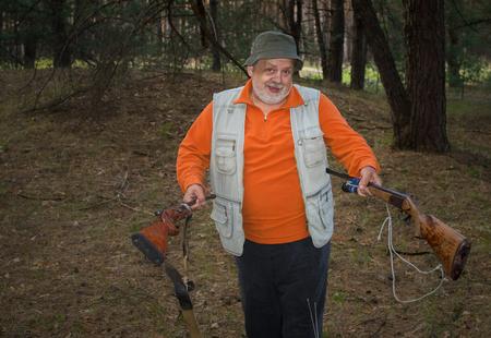 Outdoor-Porträt Senior Jäger mit zwei Gewehren im Kiefernwald