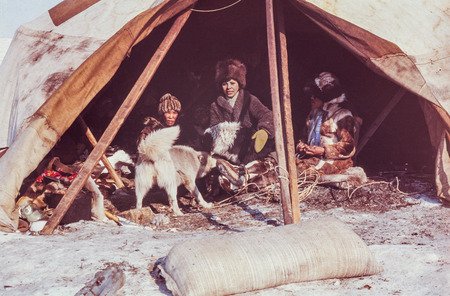 nomadism: Chukchi Peninsula, USSR - May 1983: Caucasian woman having conversation with family of the indigenous people inside of their yaranga (tent)