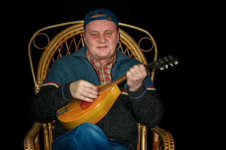 mandolin: Portrait of mature man sitting in wicker chair and playing mandolin