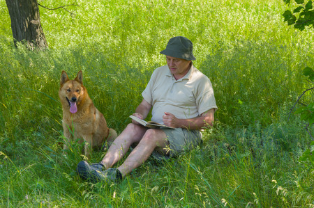 laughable: Mature man reading an interesting book to young dog under tree shadow Stock Photo