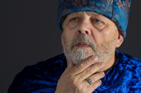 imperious: Nice portrait of meditating senior man in blue oriental clothes against dark background Stock Photo
