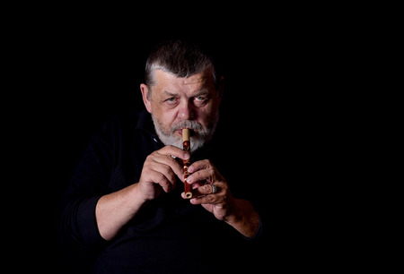 woodwind: Portrait of old musician playing Ukrainian woodwind instrument sopilka Stock Photo