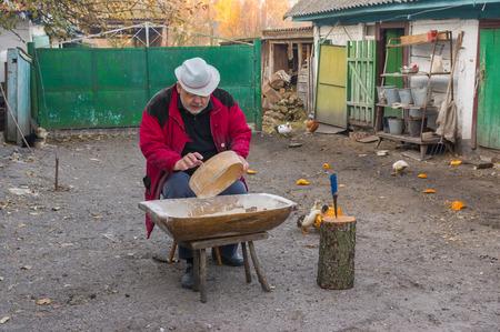 campesino: campesino ucraniano haciendo el trabajo diario (multas de pantalla de comidas) en la granja Foto de archivo