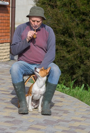 dissatisfaction: Young dog shows dissatisfaction of masters smoking while having rest in the garden Stock Photo
