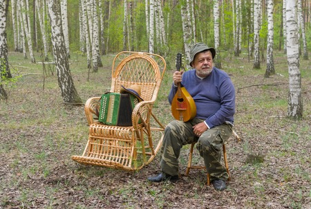 mandolin: Senior man is having rest in birch forest, sitting on a wicker stool and holding mandolin Stock Photo