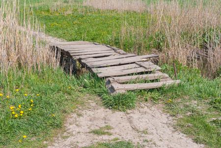 cane creek: Wooden worn foot-bridge over small stream Stock Photo