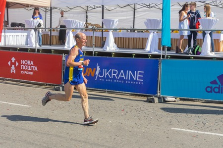 hurrying: DNEPR, UKRAINE - MAY 22, 2016:Senior participant hurrying to finish line during Interipe  Dnipro Half Marathon race on the city street at May 21, 2016 in Dnepr, Ukraine