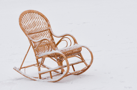 debility: Empty wicker rocking-chair on the fresh snow waiting for master