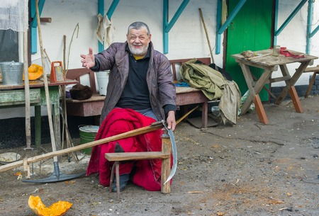 peasant: Cheerful Ukrainian peasant getting ready to whet a scythe at the homestead