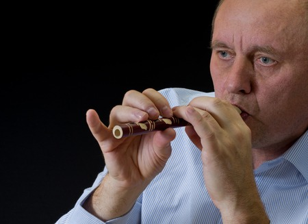 woodwind: Portrait of mature musician playing Ukrainian woodwind instrument sopilka