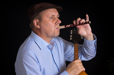 woodwind: Mature musician playing Ukrainian woodwind instrument sopilka with the right hand and taking mandolin in left one Stock Photo