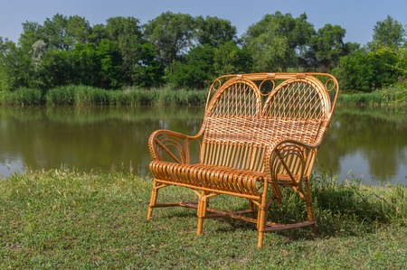 debility: Wicker wide chair on a lakeside at summer season Stock Photo