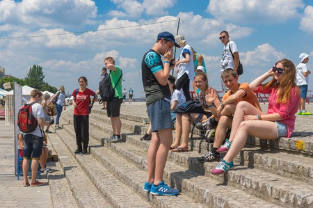 dnepr: DNEPR, UKRAINE - June 25, 2016:Group of positive young people having rest  on the Dnepr river embankment at June 25, 2016 in Dnepr, Ukraine Editorial