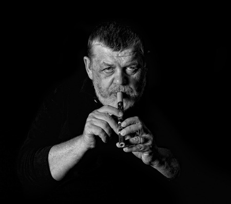woodwind: Black and white portrait of old musician playing Ukrainian woodwind instrument sopilka
