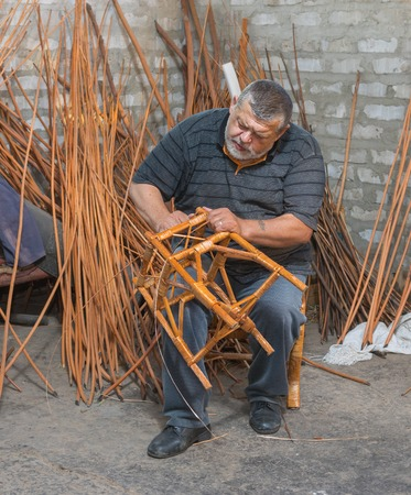 stool: Master of wicker-work making a stool Stock Photo