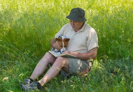 laughable: Mature man and young dog reading interesting book under tree shadow